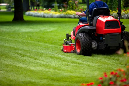 man driving a large lawn mower and cutting his lawn