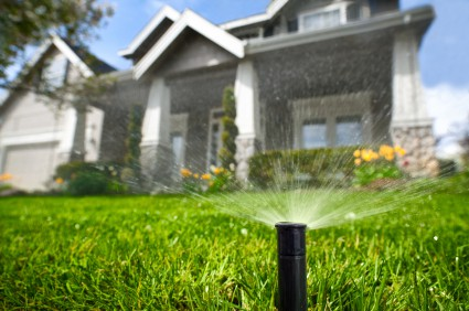 sprinkler spraying water on front lawn with a home in the background