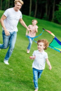 Father and children flying kite on freshly cut grass.