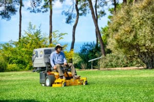 Man working on lawn mower in the public park.