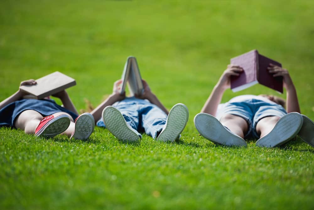 3 children reading books on freshly cut Summer grass