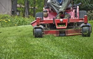 Closeup of a riding mower cutting the grass.